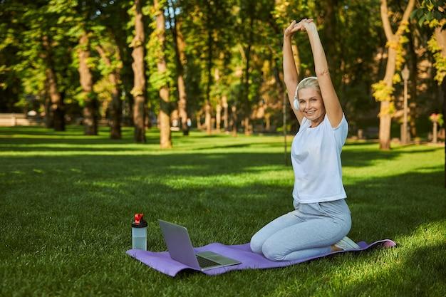 Belle Dame Sportive Dans Les écouteurs Faisant De L'exercice Et Souriant Tout En étant Assise Sur Un Tapis De Yoga Devant Un Ordinateur Portable Photo Premium