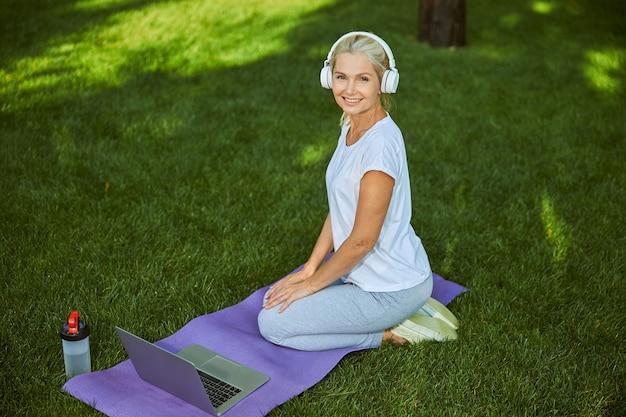 Belle dame sportive regardant la caméra et souriante assise sur un tapis de yoga avec un ordinateur portable moderne