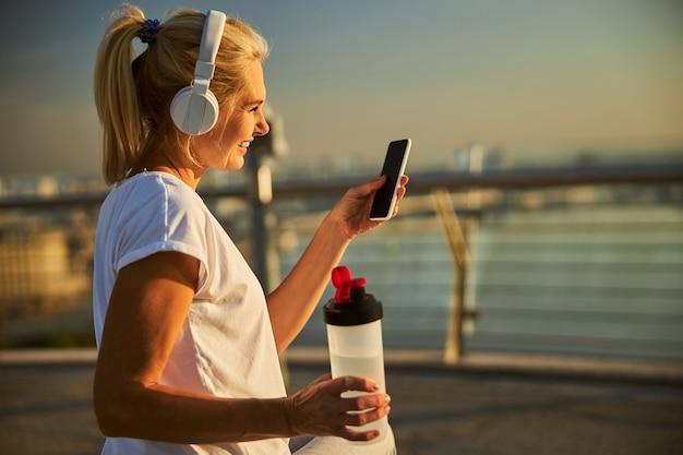 Belle dame tenant une bouteille d'eau et souriant tout en écoutant de la musique avec des écouteurs sans fil et en utilisant un smartphone