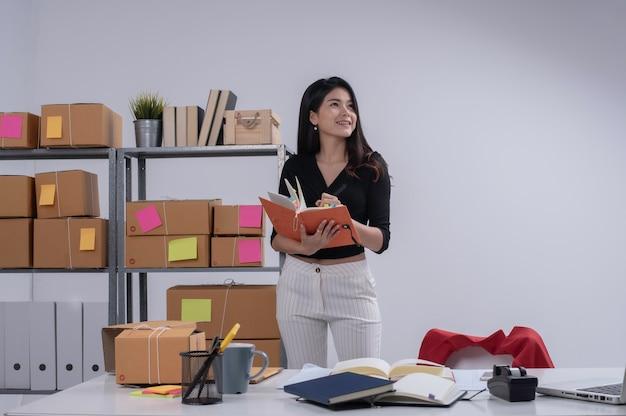 Belle dame vérification de la commande et de l'écriture sur le livre, se préparer à l'emballage, travailler le commerce électronique, femme d'affaires