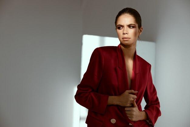 Belle dame en veste rouge sur fond sombre vue recadrée.