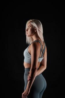 Belle dame en vêtements à la mode sportive qui pose en studio sur fond noir, femme de remise en forme, fille en forme. beaucoup d'espace de copie. mode de vie sain.