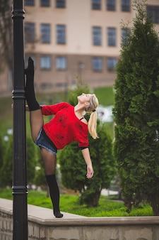 Belle danseuse de ballet ou danse acrobatique à l'extérieur dans la rue
