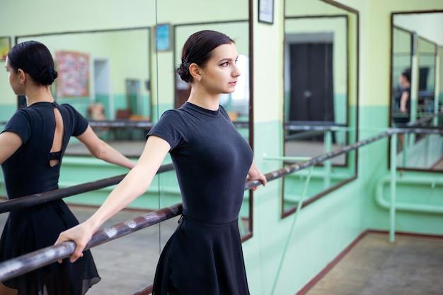 Belle danseuse debout près de la barre regard concentré