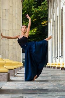 Belle danseuse gracieuse dans un haut noir et une longue jupe bleue danse dans la rue de la ville