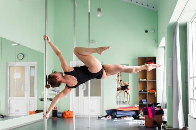 Belle danseuse de pole exécutant la pole dance dans différentes poses