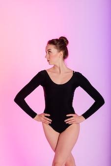 Belle danseuse portant des talons noirs et hauts tout en exécutant des tours de pole dance, néon