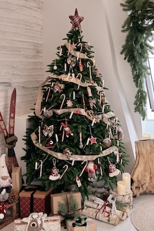 Belle décoration de maison faite à la main de bricolage. chambre confortable décorée de bougies et d'un arbre de noël avec des cadeaux en dessous. boisson chaude sur la table. intérieur du nouvel an dans un studio photo