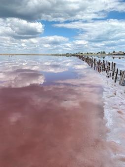 La belle eau du lac salé rose reflète les nuages et le ciel
