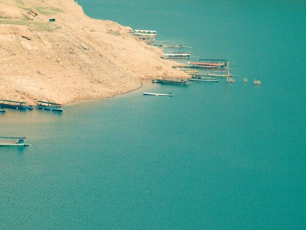 Belle eau de mer turquoise avec des bateaux et la montagne dessus photo aérienne vue de dessus