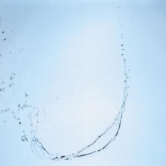 Belle éclabousse une eau propre sur fond dégradé bleu.