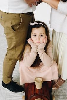 Belle écolière caucasienne assise dans un train jouet en bois devant ses parents