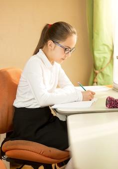 Belle écolière portant des lunettes posant derrière le bureau tout en faisant ses devoirs