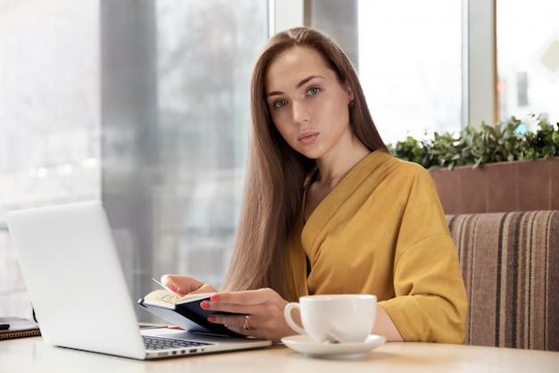 Belle élégante femme aux cheveux longs planifie votre journée en feuilletant le journal assis à une table dans le café avec un ordinateur portable et une tasse de thé