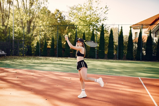 Belle et élégante fille sur le court de tennis