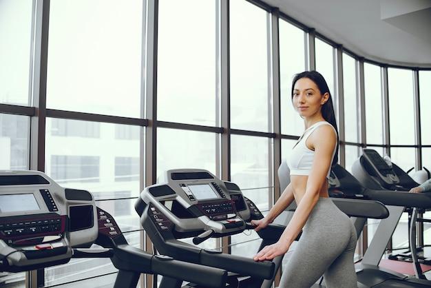 Belle et élégante fille debout dans une salle de sport