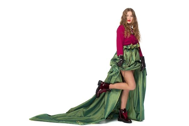 Belle élégante jeune fille adolescente aux longs cheveux bouclés dans une jolie jupe longue verte isolée sur un mur blanc.