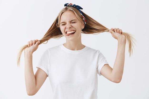 Belle élégante jeune fille blonde posant contre le mur blanc