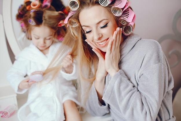 Une belle et élégante maman fait sa coiffure pour elle et sa petite fille