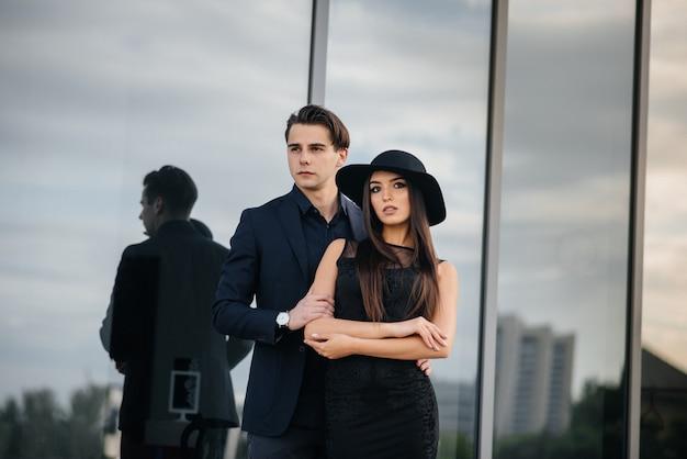 Une belle et élégante paire de jeunes en vêtements et lunettes noirs se dresse sur le fond d'un immeuble de bureaux au coucher du soleil. mode et style