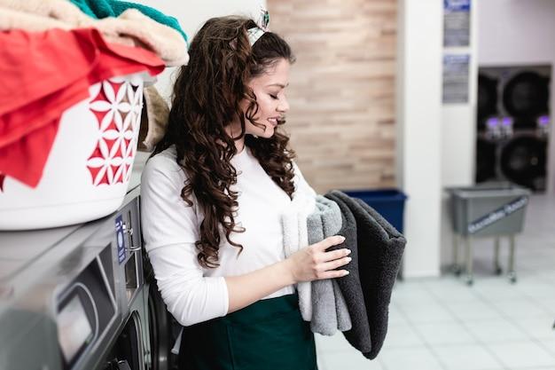 Belle employée travaillant à la laverie automatique.