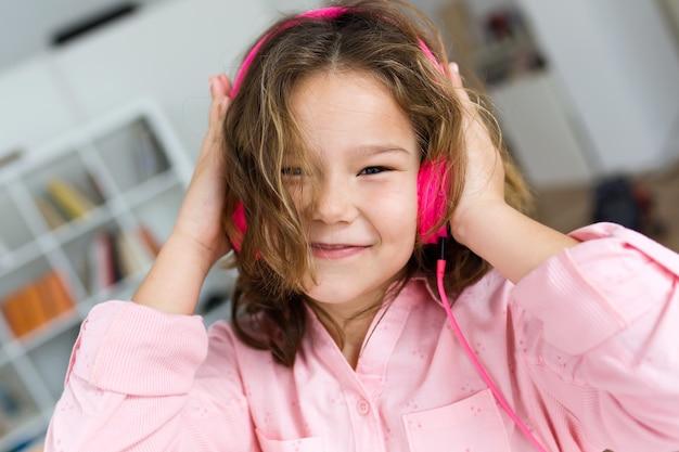 Belle enfant écoutant de la musique et de la danse à la maison.