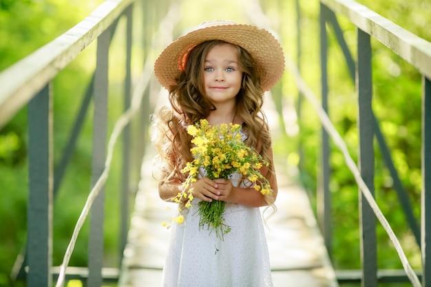 Belle enfant fille avec un chapeau de dentelle de paille sur la tête marche avec un bouquet de fleurs sauvages jaunes le long d'un sentier forestier
