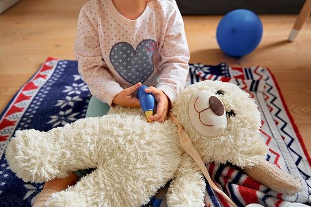 Belle avec enfant jouer au docteur à la maison. médecin de jeu d'enfant pour la conception de soins de santé. soins de santé.