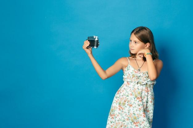Belle enfant souriante (fille) avec des dents blanches tenant un appareil photo et faisant selfie