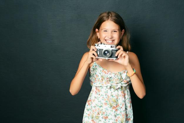 Belle enfant souriante (fille) avec des dents blanches tenant un appareil photo instantané