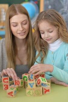 Belle enseignante avec élève jouant avec des cubes à l'école