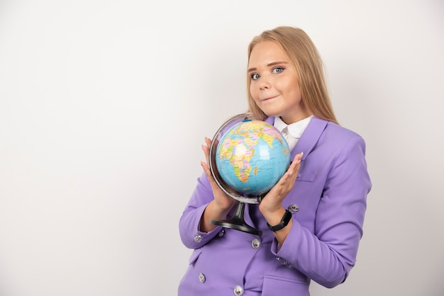 Belle enseignante tenant un globe sur un mur blanc.