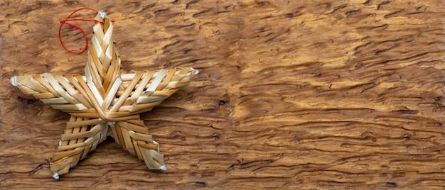 Belle étoile en fibres végétales sur fond d'artisan en bois. prêt pour les voeux de noël.