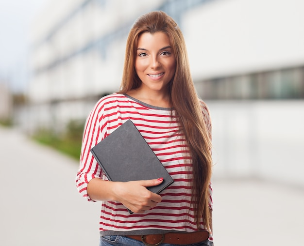 Belle étudiant posant avec bloc-notes