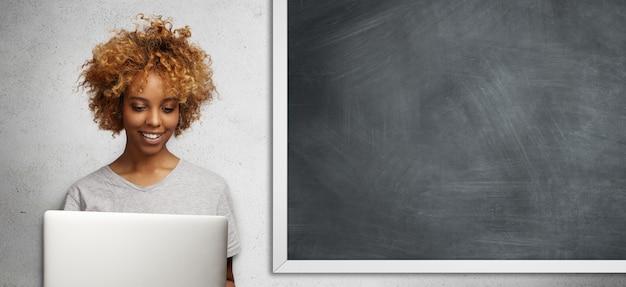 Belle étudiante africaine avec une coiffure afro à l'aide d'un ordinateur portable pour faire des recherches, se préparer à la leçon, surfer wi-fi à l'école, avec un regard enthousiaste, assis contre le tableau de l'espace de copie
