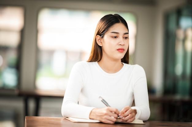 Belle étudiante asiatique s'asseoir pour l'examen à des étudiants de classe universitaire assis dans la rangée éducation style de vie collège universitaire