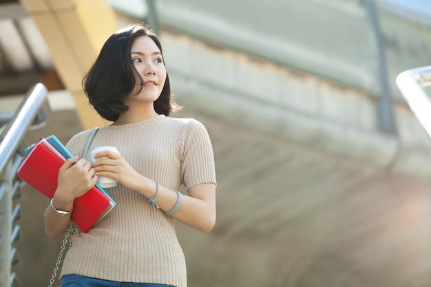 Belle étudiante asiatique tenant ses livres et une tasse de café debout