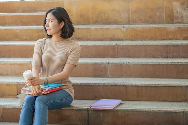 Belle étudiante asiatique tenant ses livres et une tasse de café