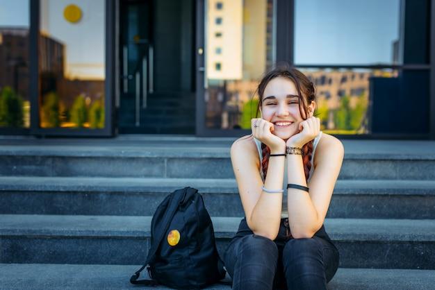Belle étudiante assise sur les marches et souriant