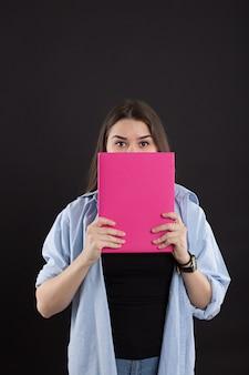 Belle étudiante en chemise en jean aux cheveux longs, sur un mur noir, jetant un œil par derrière le livre