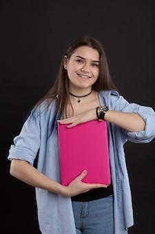 Belle étudiante en chemise en jean aux cheveux longs, sur mur noir, livre montre