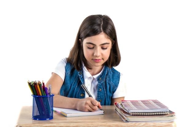 Une belle étudiante est assise au bureau et écrit la lettre. fond blanc.