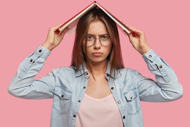 Une belle étudiante européenne sérieuse tient un livre au-dessus de sa tête, se sent fatiguée du matériel d'apprentissage pour l'examen, a une expression insatisfaite, ne veut pas étudier, isolée sur un mur rose.