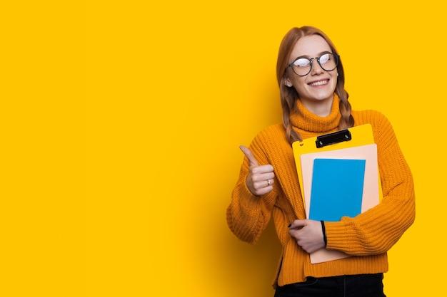 Belle étudiante fait signe le même signe sur un mur jaune