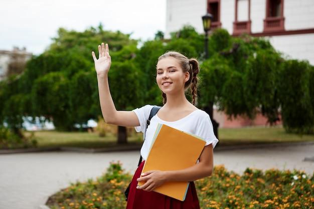 Belle étudiante joyeuse souriant, saluant, tenant des dossiers à l'extérieur