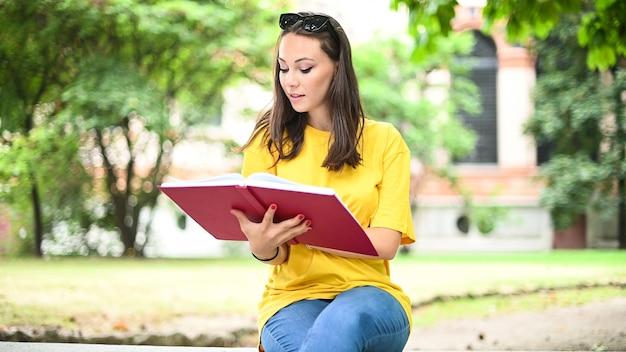 Belle étudiante en lisant un livre sur un banc dans un parc