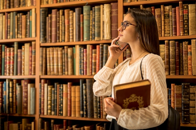 Belle étudiante avec des livres parlant au téléphone dans la bibliothèque