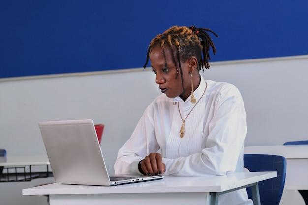Une belle étudiante noire qui étudie à l'aide d'un ordinateur portable