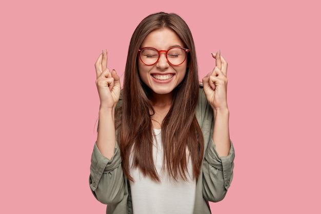 Belle étudiante posant contre le mur rose