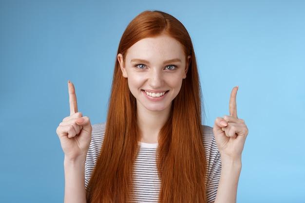 Une belle étudiante rousse déterminée entre dans la décision finale du collège en pointant vers le haut les index levés en toute confiance, souriant, les dents blanches ont l'air affirmées de la caméra en donnant des recommandations sur ce qu'il faut choisir.